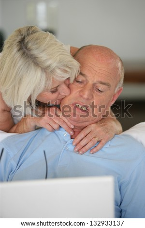 mature lady kissing her husband browsing with laptop - stock photo