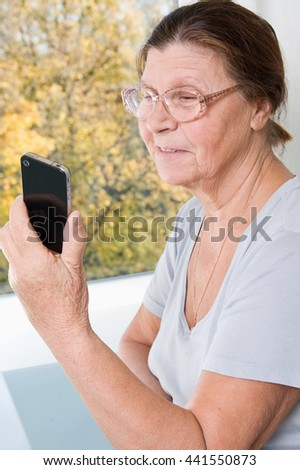 Mature looking at mobile phone and smiling. - stock photo