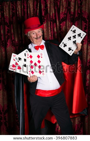 Mature magician on stage performing a magic trick with cards - stock photo
