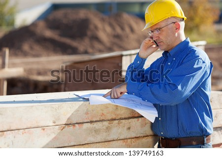 Mature male architect pointing at blueprint while using phone at construction site - stock photo