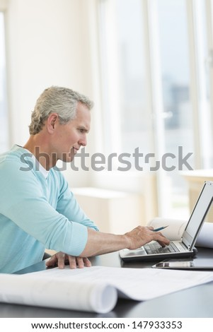 Mature male architect using laptop at desk in office - stock photo