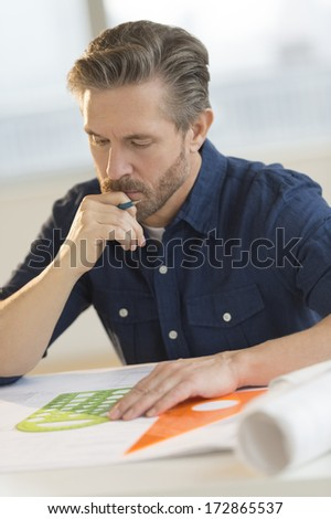 Mature male architect working on blueprint at desk in office - stock photo