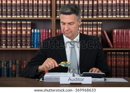 Mature male auditor scrutinizing financial documents at table in office - stock photo