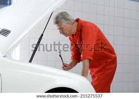 Mature male car mechanic, in red overalls, looking at car engine in auto repair shop, holding wrench, side view - stock photo