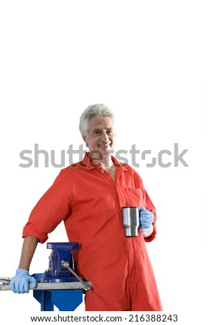 Mature male car mechanic, in red overalls, taking tea break, smiling, portrait, cut out - stock photo