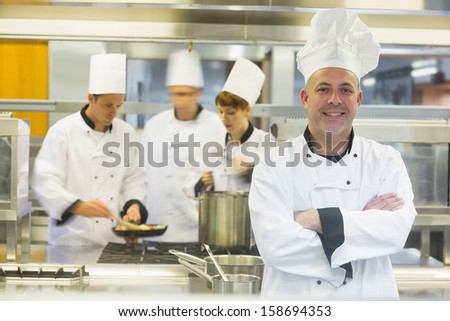 Mature male chef posing with crossed arms while colleagues working in the background  - stock photo