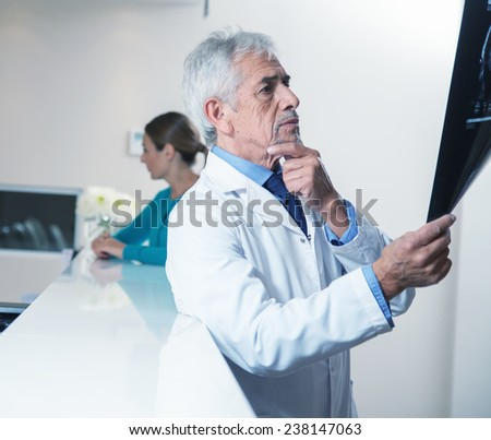 Mature male doctor analyzing x-ray test, doctor and assistant in background. - stock photo