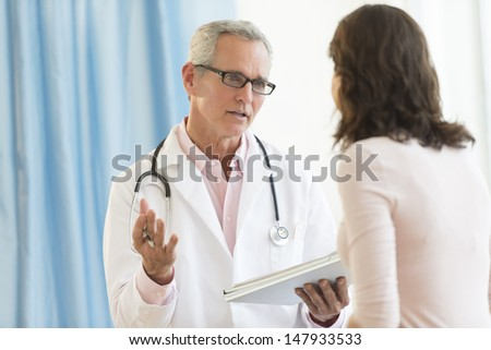 Mature male doctor discussing with female patient in clinic - stock photo