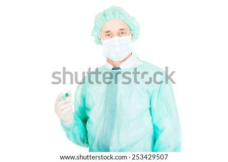 Mature male doctor holding a syringe. - stock photo