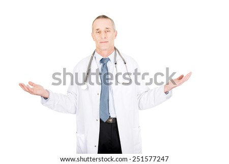 Mature male doctor holding copyspace in both hands. - stock photo