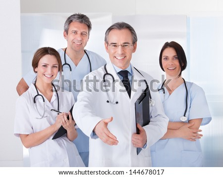 Mature Male Doctor Offering Handshake In Front Of His Colleague - stock photo