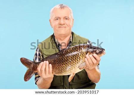 Mature male fisherman holding a freshwater fish on blue background - stock photo