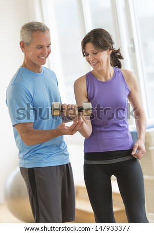 Mature male instructor guiding woman in weightlifting at health club - stock photo
