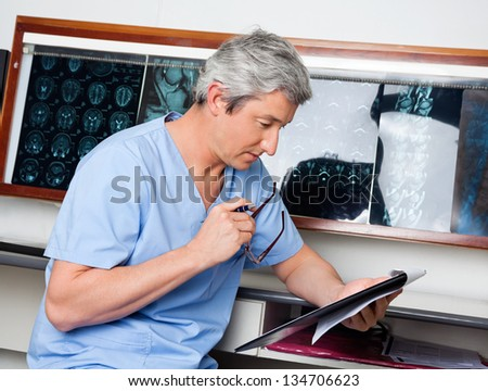 Mature male medical professional in uniform reading document at clinic - stock photo