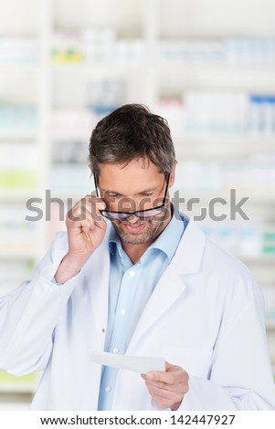 Mature male pharmacist reading prescription at pharmacy counter - stock photo