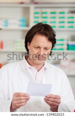 Mature male pharmacist reading prescription paper in pharmacy - stock photo