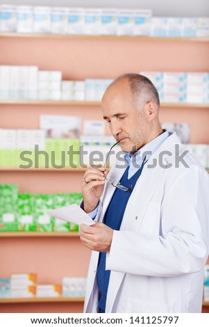 Mature male pharmacist standing in front of medicine looking prescription - stock photo