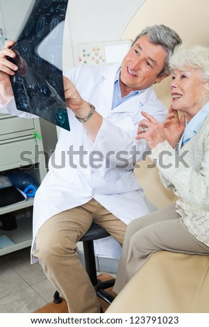 Mature male radiologist explaining CT scan x-ray to senior female patient - stock photo