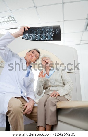Mature male radiologist with senior female patient looking at x-ray - stock photo