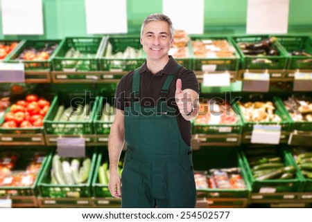 Mature Male Sales Clerk Showing Thumb Up Gesture In Supermarket - stock photo