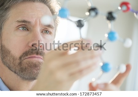 Mature male scientist analyzing molecular structure in laboratory - stock photo