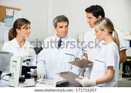 Mature male scientist with students taking notes in medical laboratory - stock photo