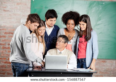 Mature male teacher with laptop explaining lesson to group of students at desk in classroom - stock photo