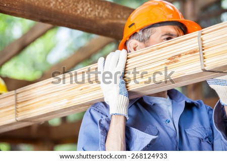 Mature male worker carrying tied wooden planks at construction site - stock photo