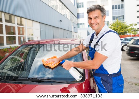 Mature male worker cleaning car windshield with cloth and spray bottle - stock photo