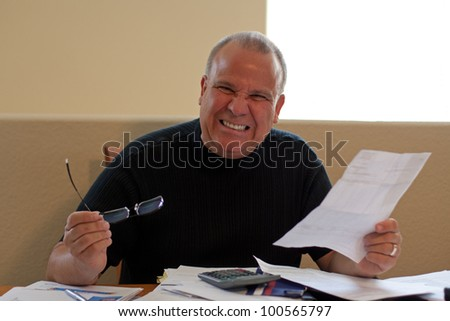 mature male worried and frustrated about bills - stock photo
