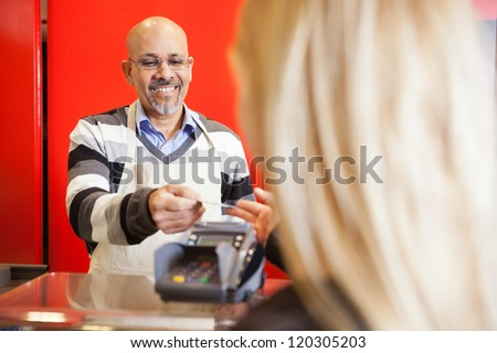 Mature man accepting credit card from young woman for payment of purchases - stock photo
