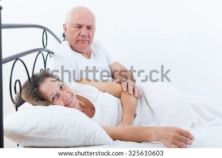 Mature man and woman on   bed in   bedroom. - stock photo