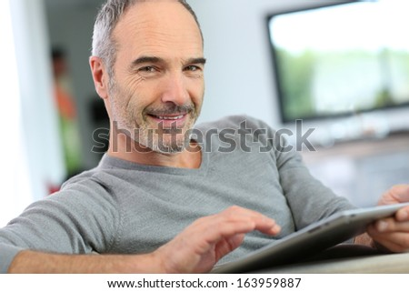 Mature man at home websurfing on internet  - stock photo