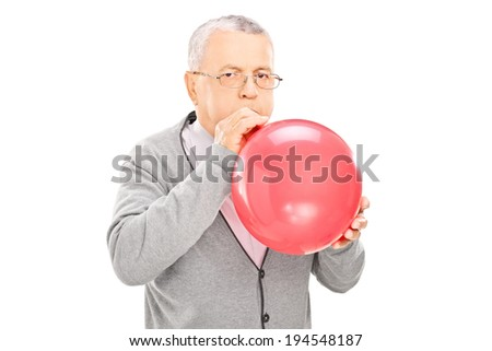 Mature man blowing up a balloon and looking at camera isolated on white background - stock photo