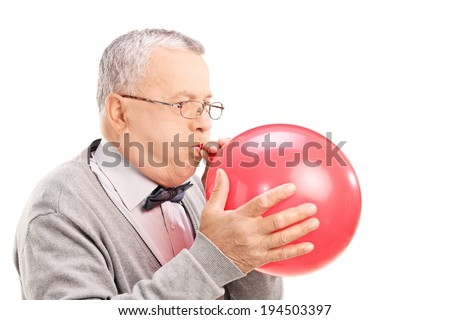Mature man blowing up a balloon isolated on white background - stock photo