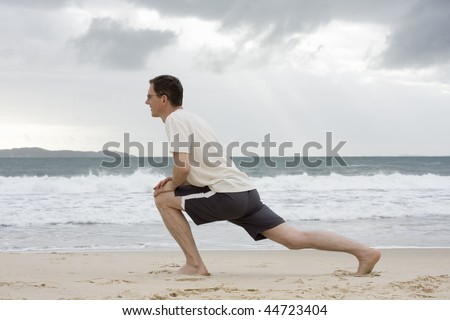 Mature man doing fitness exercises on a beach - stock photo