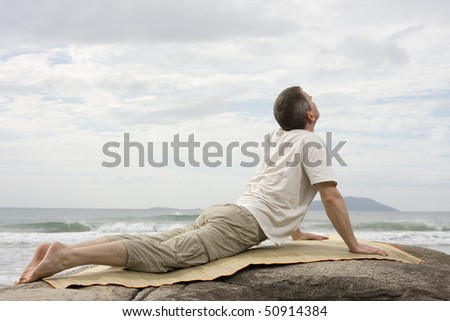 Mature man doing yoga exercises on a rock at the sea - stock photo