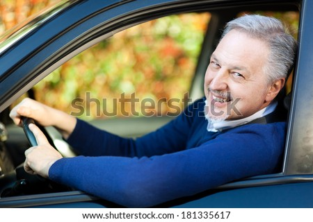 Mature man driving his car - stock photo