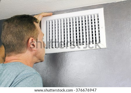 Mature man examining an outflow air vent grid and duct to see if it needs cleaning. One guy looking into a home air duct to see how clean and healthy it is. - stock photo
