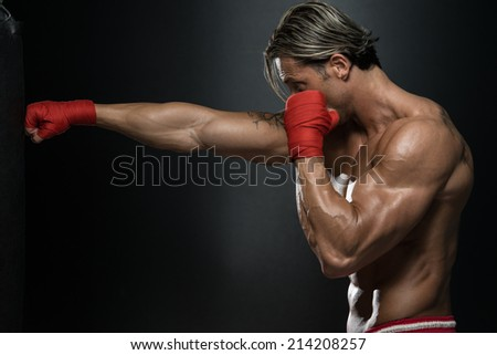 Mature Man Exercising Bag Boxing In Studio - A Man With A Tattoo In Red Boxing Gloves - Boxing On Black Background - The Concept Of A Healthy Lifestyle - The Idea For The Film About Boxing - stock photo