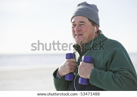 Mature man exercising with hand weights on beach staying fit - stock photo