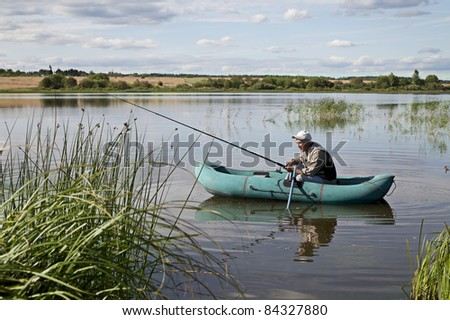 Mature Man Fishing From a inflatable boat - stock photo