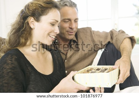 Mature man giving  a woman a box of chocolates at home. - stock photo