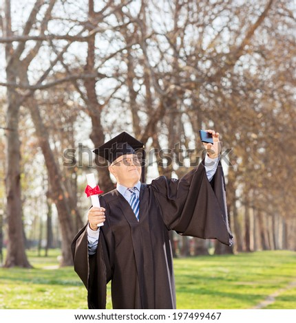 Mature man holding diploma and taking selfie in park shot with tilt and shift lens - stock photo