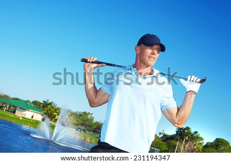 Mature man holding golf club on course against clear blue sky - stock photo