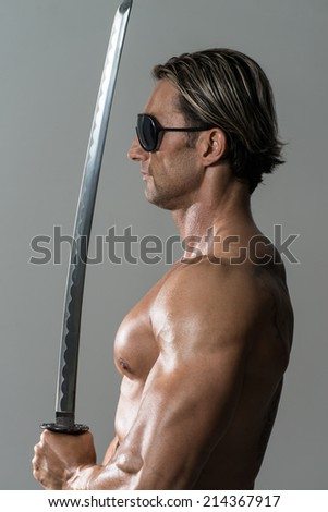 Mature Man Holding Warrior Sword - Portrait Of A Handsome Muscular Ancient Warrior With A Sword - stock photo