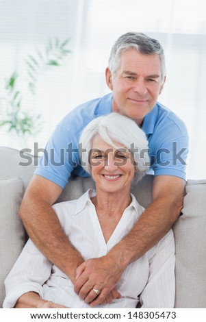 Mature man hugging his wife who is sitting on the couch - stock photo