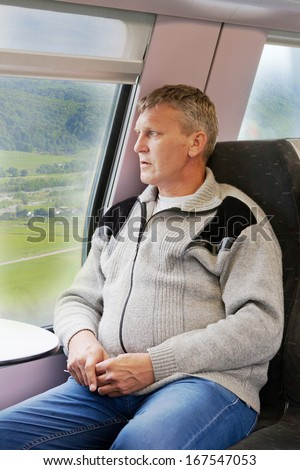 mature man in a gray cardigan sits in a car of a train and looks out of the window - stock photo
