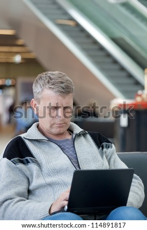 mature man in a waiting room of the modern international airport - stock photo