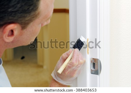 Mature man in his forties about to paint a white door jam with touch up paint.  Caucasian guy about to spread white paint on a doorway where the paint was chipped off. - stock photo